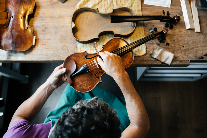 Overhead shot of a mature male violin maker repairing an old violin on his workbench.